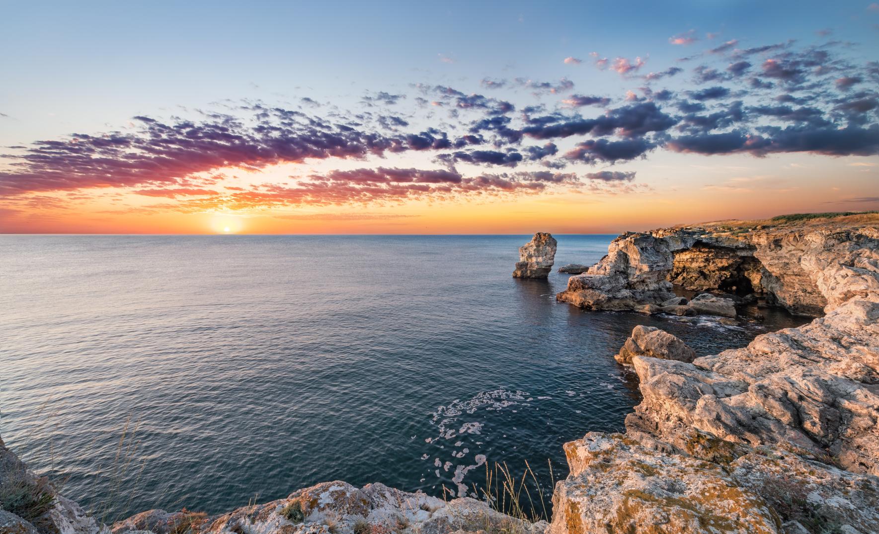 Beautiful seascape. Sea and rock at the sunrise. Nature composit